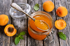 Jam from apricots. In a glass jar on a wooden surface Royalty Free Stock Photo