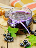 Jam blackcurrant with a napkin on board Stock Photos