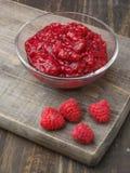 Jam bowl with ripe raspberries on wood Stock Photos