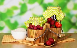 Jam, buckets with raspberry and strawberry. A cup with sugar a spoon with berries and napkin on a table Royalty Free Stock Photos