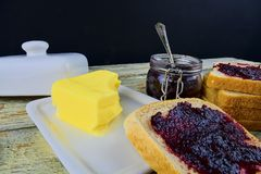 Jam, butter in butter dish and jam spread on toast. Healthy and diet concept. Rural white wooden background. royalty free stock photography