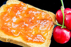 Jam, cherries and bread Stock Photography