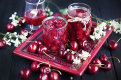 Jam from cherry, in cans. winter desserts. dark photo. spring white flowers. Jam from cherry, in cans. winter desserts. dark photo. spring white flowers royalty free stock photos