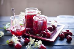 Jam from cherry, in cans. winter desserts. dark photo. spring white flowers.  royalty free stock photography