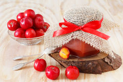 Jam, confiture of Malpighia glabra (red acerola) in jar and fres. H fruitsin bowl. Selective focus on bow Stock Image