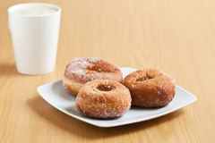Jam doughnuts with coffee. Three jam doughnuts on a white plate with coffee in the background on a wooden surface Stock Images