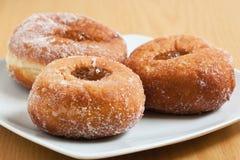 Jam doughnuts on a white plate. Three jam doughnuts on a white plate on a table Stock Image