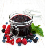 Jam and fresh berries. On a wooden background Stock Photos