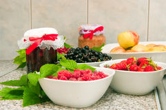 Jam and fresh fruit. The image of jars with jam and fresh berries on a wooden table Stock Photography