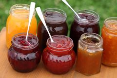 Jam. Glass with strawberry, cherry, orange, plum, blackcurrant and peach jam and spoons Royalty Free Stock Photography