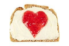 Jam heart on bread. Heart shape made of red jam on a slice of bread with butter Royalty Free Stock Image
