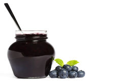 Jam jar with blueberry jam a spoon and blueberries Stock Images