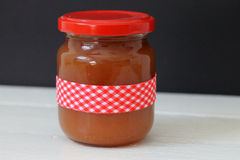 Jam in jar. Jam in a jar decorated with a red plaid ribbon Royalty Free Stock Photo