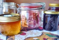 The jam jelly shelf. Money hidden between the food jars Royalty Free Stock Photography