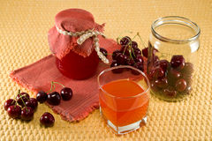 Jam and juice from cherries. Berries cherries, jam and juice on a napkin on the table Royalty Free Stock Photo