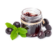 Jam made from black raspberries Cumberland in glass jar. And leaves of mint  on white background Royalty Free Stock Photography