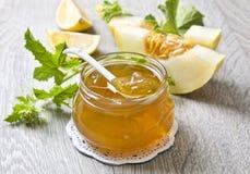 Jam melon. Glass jar with melon jam, melon slices on a wooden background stock photo