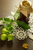Jam nuts with crochet lace and young green nuts fruit Stock Photos