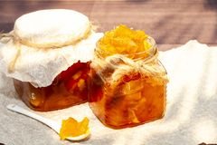 Jam from oranges, lemons, pumpkins. Jam on a spoon and in a jar on a wooden background. Appetizing jam of orange color in a jar an
