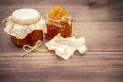Jam from oranges, lemons, pumpkins. Jam on a spoon and in a jar on a wooden background.