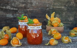 Jam of physalis and orange on an old wooden table Royalty Free Stock Photos
