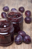 Jam from plums in two glass jars Stock Photos