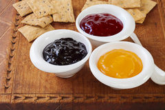 Jam Selection for Tasting. Selection of jams with crisp biscuits for tasting on an old wooden board. Blackcurrant jam, strawberry jam, lemon curd Stock Photo