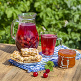 Jam shortbread cookies and red compote with cherries, strawberries, gooseberries, raspberries and apricot jam Stock Photo