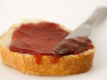 Jam spread and knife. Slice of bread with jam spread and knife on white background Royalty Free Stock Photography
