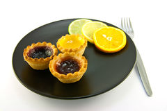 Jam Tarts with Citrus Slices and Fork. Red and yellow small jam tarts with slices of lemon, lime, and orange on a black plate with a fork on a white background Royalty Free Stock Photo