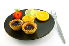 Jam tarts and Fruit. Red and yellow small jam tarts with slices of lemon, lime, orange and strawberry on a black plate with fork on a white background Stock Images