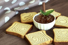 Jam and toast on a wooden board. Apple jam with cinnamon and toast on a wooden stand Royalty Free Stock Image