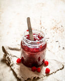 Jam from wild raspberries in the jar. On rustic background Stock Image