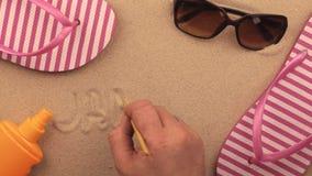 Jamaïca-inschrijving die met de hand op het zand, onder strandtoebehoren wordt geschreven stock footage