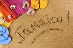 Jamaica beach  sand word writing. Jamaica beach background with towel and flip flops (studio shot - directional light and warm color are intentional Royalty Free Stock Photography
