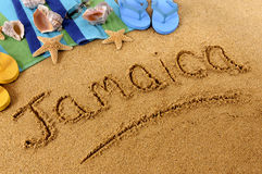 Jamaica beach sand word writing. The word Jamaica written on a sandy beach, with seashells, beach towel, starfish and flip flops Royalty Free Stock Image