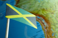 Jamaica flag with a globe map as a background. Macro stock image