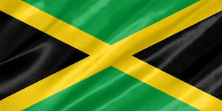 Jamaica Flag. With waving on satin texture stock photography