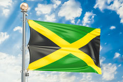 Jamaica flag waving in blue cloudy sky, 3D rendering Royalty Free Stock Photo