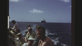 Tourists In A Lifeboat On A Tour To Coast. JAMAICA, MAY 1971. Two Shot Sequence. Group Of Tourists In A Lifeboat On A Tour To Coast With The Russian Cruise Liner stock video footage