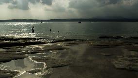 Jamaica strand på Sirmione, Italien, på skymning Arkivfoton