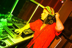 Jamaica theme DJ. Jamaica dressed disc jockey hard at work at a nightclub. Vivid colours royalty free stock photography