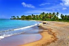 Jamaica. Un barco nacional en costa arenosa de una bahía Imagen de archivo