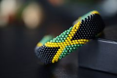Jamaican flag bead crochet bracelet on a dark bakground. Close up stock photography