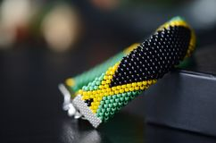 Jamaican flag bead crochet bracelet on a dark bakground. Close up royalty free stock photo