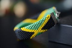 Jamaican flag bead crochet bracelet on a dark bakground. Close up stock photos