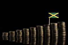 Jamaican flag with lot of coins on black. Background stock photo