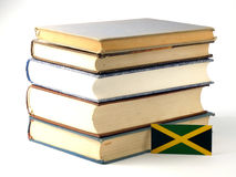 Jamaican flag with pile of books on white background. Jamaican flag with pile of books on white stock photos
