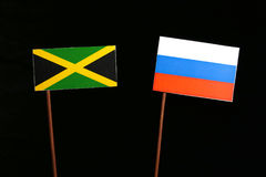 Jamaican flag with Russian flag on black. Background stock photos