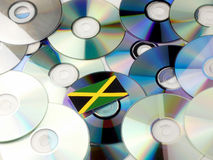 Jamaican flag on top of CD and DVD pile isolated on white. Jamaican flag on top of CD and DVD pile isolated Royalty Free Stock Photos